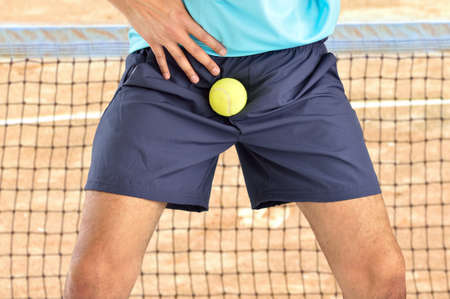 man playing tennis being hit by a tennis ball with force in the crotch when he misses a catch or as an unexpected accident on a clay court