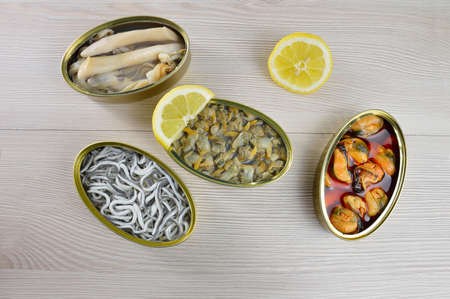 Assortment of cans of canned with different types of fish and seafood on rustic wooden table