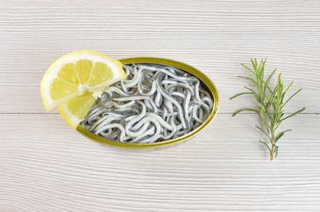 High angle shot of delicious can of preserved eels on on rustic wooden table with lemon