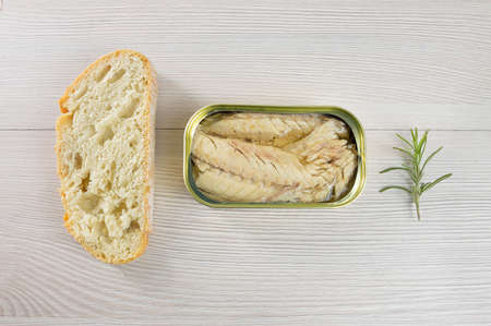 Canned mackerel and bread on rustic wooden table