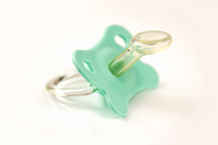 Green baby's pacifier isolated on white background