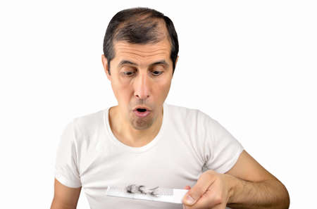 Man holding comb looking at loss hair with gray background