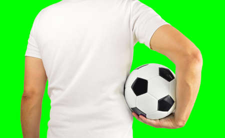 Cropped rearview image of a young man holding a soccer ball under his arms.Isolated cutout on green background with chroma key.Rearview Banco de Imagens