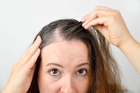 woman is checking white hair while looking at the mirror Stock Photo