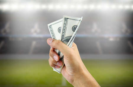 Close up of a man's hand crushing a wad of hundred dollar bills in concept of getting money with bets in soccer Banco de Imagens