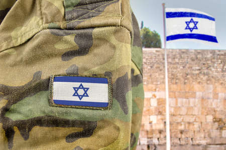 Military man posing in front of Israel flag and The Western Wall background in jerusalem