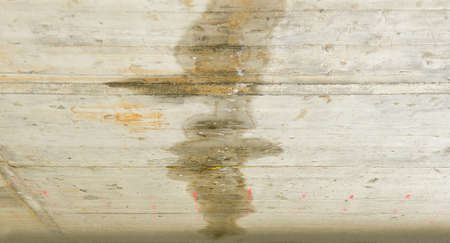 Rain water leaks on the roof causing damage Stock Photo