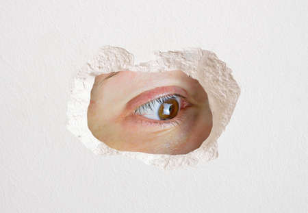 eye looking wall hole close up trapped