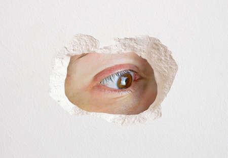 occhio che guarda il foro nel muro da vicino intrappolato