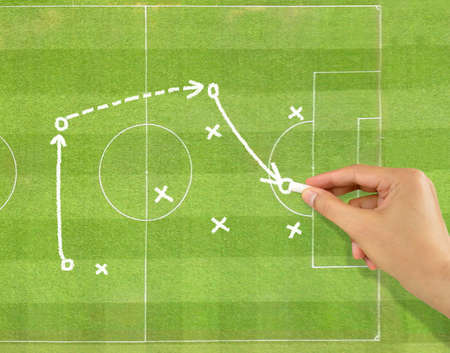 hand of a football coach drawing a tactics of soccer game with white chalk on field background