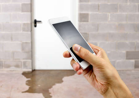 A hand holding up a smart phone with water damage in basement caused by sewer backflow due to clogged sanitary drain background Stock Photo