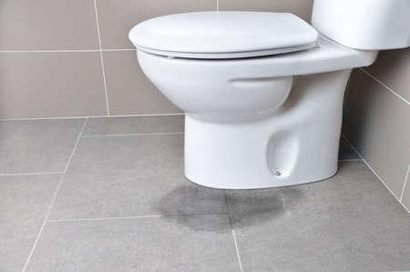 Lekkage van water uit een toilet door verstopping van de leiding Stockfoto