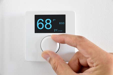 Mans hand adjust thermostat digital in fahrenheit at home
