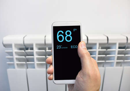 Close up of a person hand adjusting temperature on thermostat through smart phone at home Stock fotó