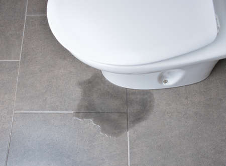 Leakage of water from a toilet due to blockage of the pipe Stock Photo