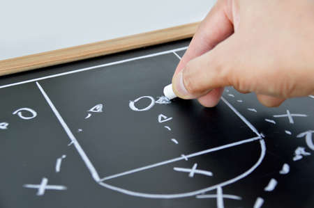 hand of a basketball coach drawing a game tactics with white chalk on blackboard Stok Fotoğraf