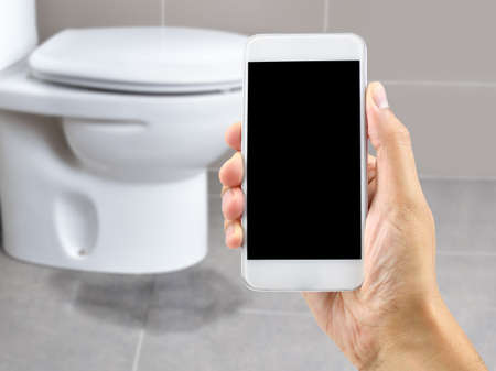 A hand holding a smartphone to call the professional to repair a water leak in the toilet