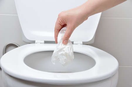 hand of a person who drop tissue paper in the toilet bowl Stockfoto