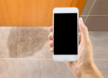 A hand holding a smartphone to call the professional to repair a water leak in the room Stok Fotoğraf