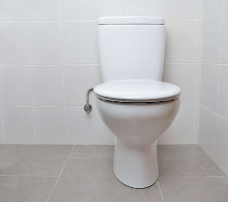 White toilet bowl in a bathroom with the lid closed