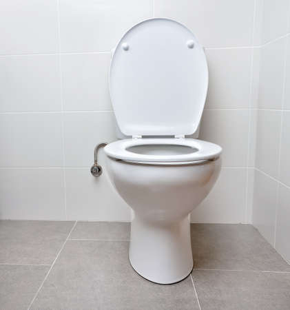 White toilet bowl in a bathroom with the lid open