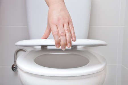 hand of a woman closing the lid of a toilet Imagens