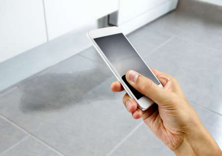 A hand holding a smartphone to call the professional to repair a water leak in the kitchen room