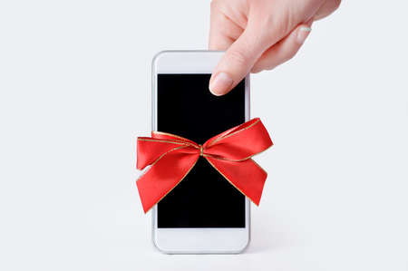 hand holding a phone gift with a red ribbon and white background Stok Fotoğraf