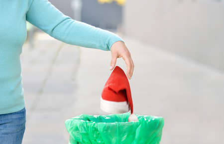 Woman throwing a santa hat to the trash in a trash bin a city after Christmas Stok Fotoğraf