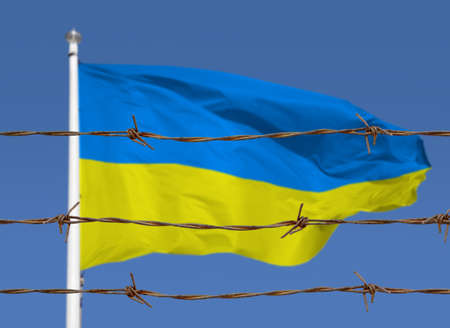 Metal fence with barbed wire on a ukrainian flag. Separation concept, borders protection.Social issues on refugees or illegal immigrants