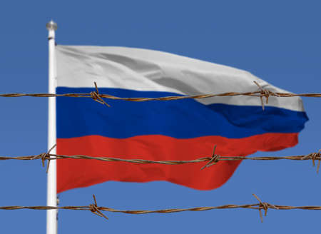 Metal fence with barbed wire on a russian flag. Separation concept, borders protection.Social issues on refugees or illegal immigrants