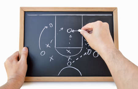 hand of a basketball coach drawing a game tactics with white chalk on blackboard over white background Stok Fotoğraf