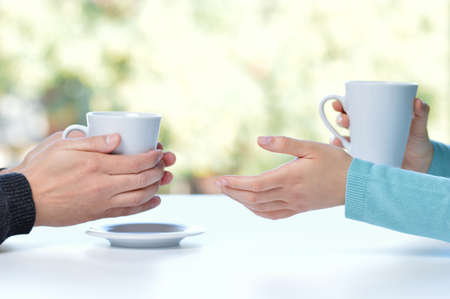 Back light profile of hands of two friends or couple talking holding coffee cups sitting in a table at home with a window in the background