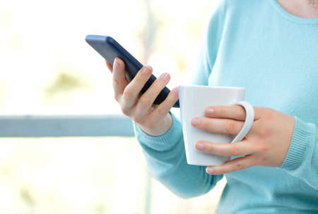 Woman hands holding a coffee mug with phone