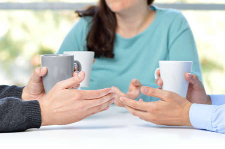 Three friends talking and holding coffee cups Stok Fotoğraf