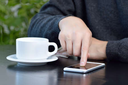 Closeup shot of a young man using a cellphone and drinking a coffee while sitting in a cafe
