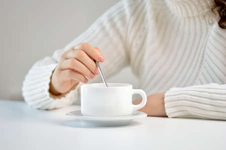 Closeup shot of an unrecognizable woman preparing a cup of coffee