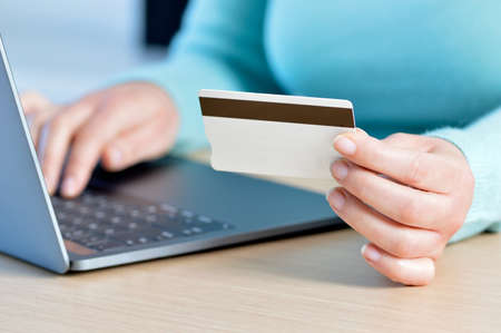 Close up of a woman hands buying online with a credit card and a laptop in Ecommerce concept