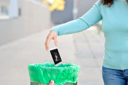 Woman throwing  her broken phone into the garbage in a trash bin at street