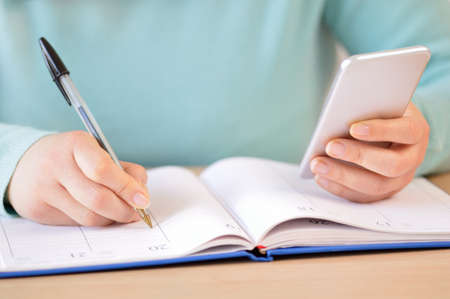 Close up of woman hand writing in agenda consulting a mobile phone on a desk at home or office