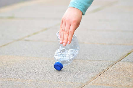 Close up of woman hand  picking a plastic bottle on the floor in the street with copy space