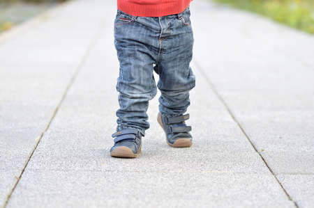 Cropped image of the legs of a baby walking at street