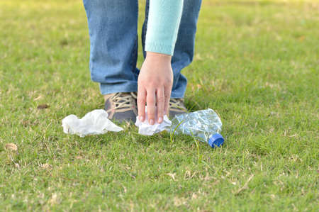 Close up of eco hiker hand collecting garbage in the grass of the mountain Banque d'images