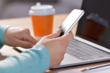 Girl hands using a smart phone and a laptop on a desk with a coffee drink Banque d'images