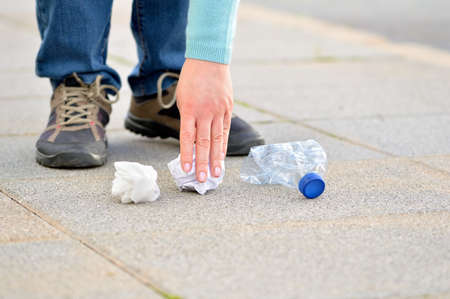 Close up of woman hand collecting garbage on the floor in the street with copy space