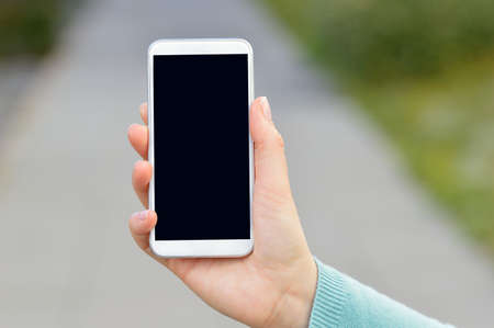 Cropped shot of an unrecognizable young woman using a smartphone outside