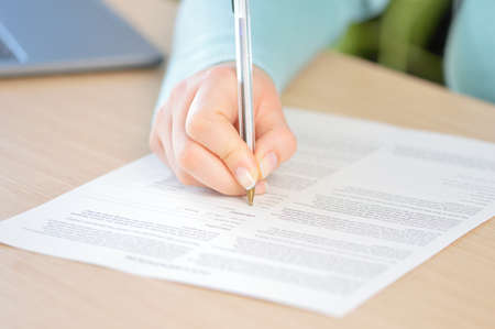 Close up of a woman hand writing or signing in a document on a desk at home or office Banque d'images