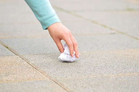 Close up of woman hand  picking a paper on the floor in the street with copy space