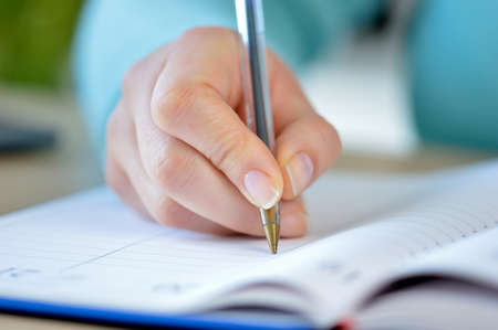 Close up of woman hand writing in an agenda at home