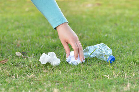 Close up of woman hand collecting garbage of the grass in the mountain with copy space